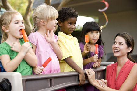 popsicles: Diverse group of preschool 5 year old children playing in daycare with teacher Stock Photo