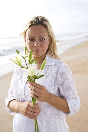 Young pretty pregnant woman wearing white on beach holding flower photo