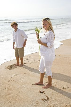 Young pretty pregnant woman wearing white on beach holding flower with husband photo