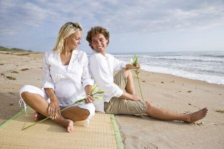 Gelukkige jonge zwangere paar ontspannen op het strand samen zitten op zand  Stockfoto