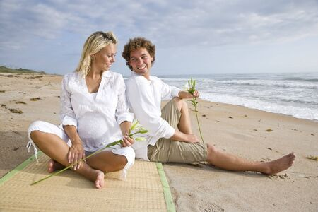 Happy young pregnant couple relaxing on beach sitting together on sand Stock Photo