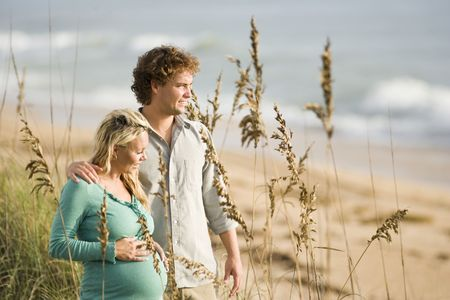 Happy young pregnant woman at beach with husband photo