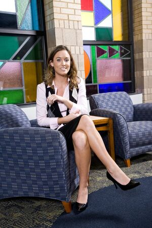 Attractive happy young woman wearing skirt sitting in armchair in reception area Stock Photo - 6799424