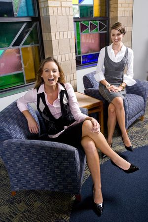 Attractive happy young women wearing skirts sitting in armchairs in reception area
