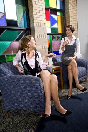 Attractive happy young women wearing skirts sitting in armchairs in reception area photo