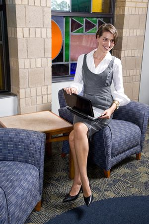 Attractive happy young woman sitting on armchair with laptop in reception area photo