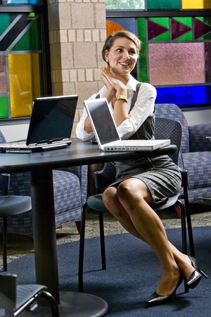 Pretty young woman waiting at table with laptop computers photo