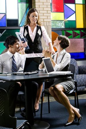 conversing: Three office workers meeting and conversing in colorful boardroom Stock Photo