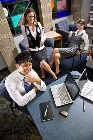 Male office worker with laptop, female coworkers sitting and relaxing in background photo