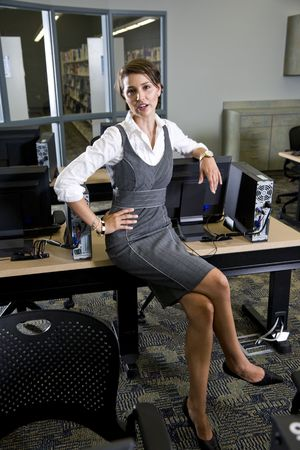 Young woman, librarian, teacher or university student sitting in library computer room photo