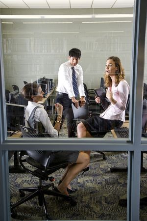Three teachers conversing in library computer room