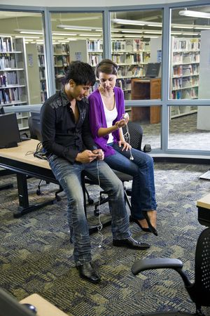 Two university students looking at music players in school library photo