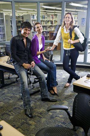 estudiantes universitarios: Tres estudiantes universitarios, mirando de reproductores de m�sica en la biblioteca de la escuela