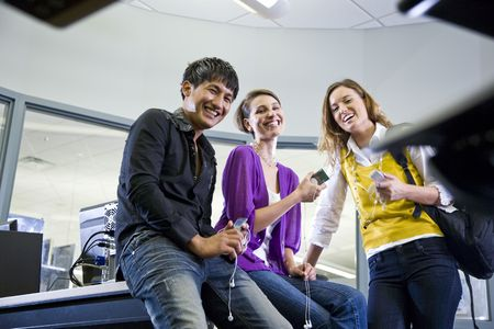 Three university students looking at music players in school library photo