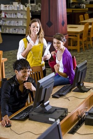 Male college student using computer with two pretty female students watching photo