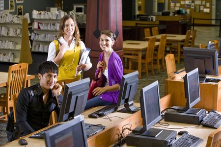 Two pretty female university students with male student using computer in library