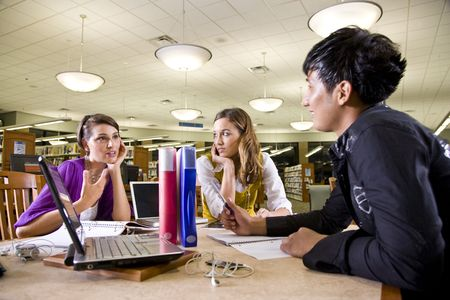pc: Two pretty female college students studying with handsome male student in school library Stock Photo