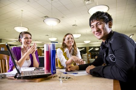 Two pretty female college students studying with handsome male student in school library photo