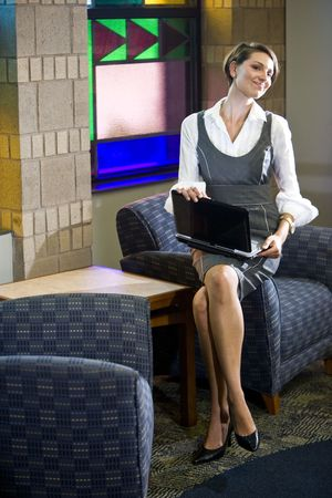 Attractive happy young woman sitting on armchair with laptop in reception area