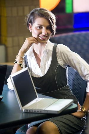 Pretty young woman waiting at table with laptop computers
