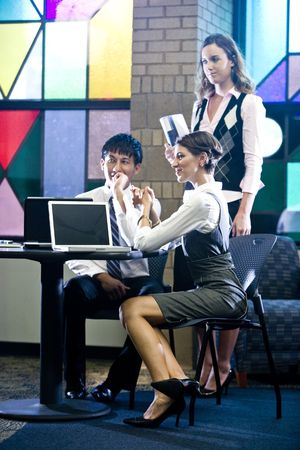 Three office workers meeting and conversing in colorful boardroom photo