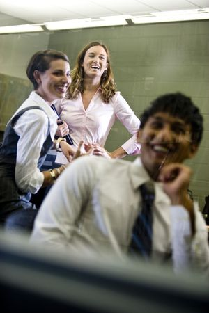 Three university students conversing and hanging out in classroom Stock Photo - 6799444