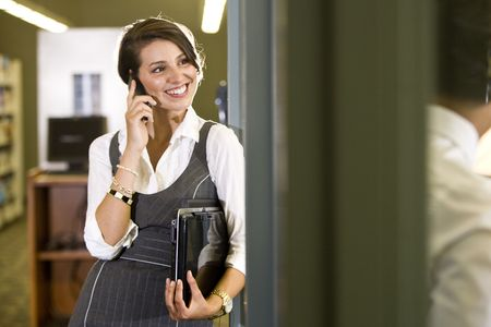 Happy female university student at library doorway using mobile phone holding laptop photo