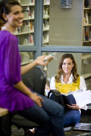 Two female university students conversing in library photo