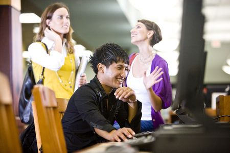 conversing: Male college student using computer and conversing with two pretty female students Stock Photo