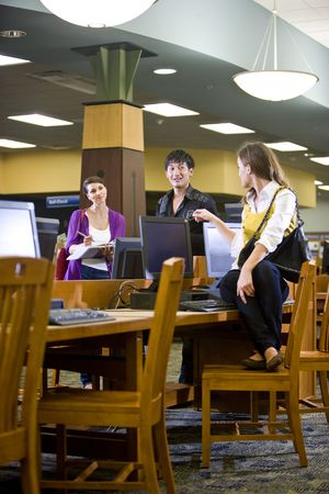 Three university students hanging out in school library by computers photo