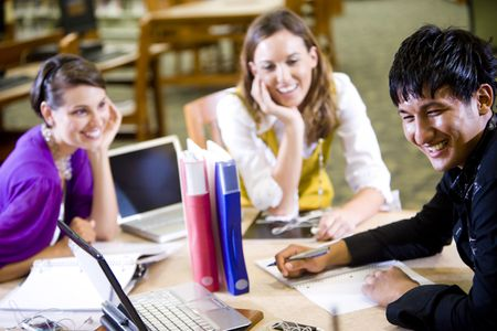 Male college student studying with two pretty female students in school library photo