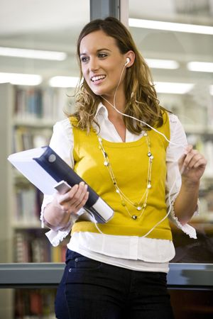 Close up of pretty female university student hanging out in school library listening to music player photo