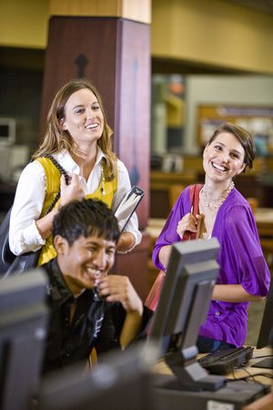 Two pretty female university students watching male student use computer in library photo