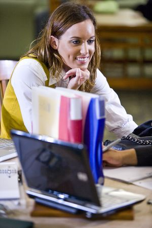 Pretty female university student studying at table in school library photo