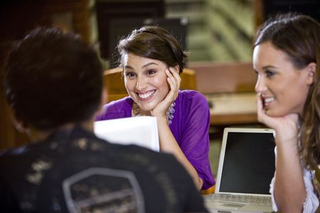Pretty female college student and friend focusing attention on male student Stock Photo