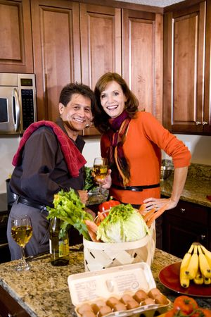 Mature couple in kitchen enjoying white wine while preparing dinner photo