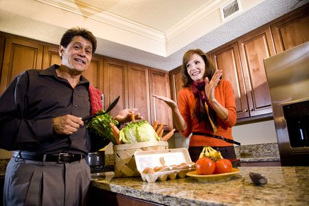 Mature couple laughing in kitchen, husband cooking dinner photo
