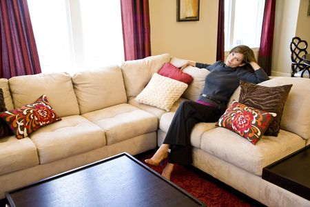 woman on couch: Attractive mature woman relaxing on couch in elegant modern living room Stock Photo