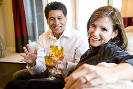 Mature couple drinking white wine together on living room sofa, focus on woman in foreground photo