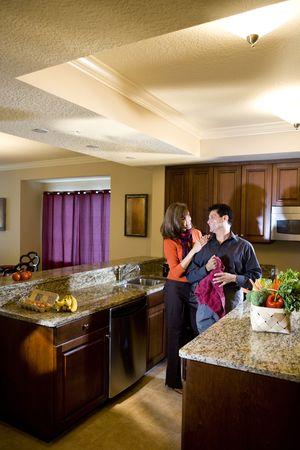 中高年カップルお互いの愛情を込めて見て台所で一緒に立って