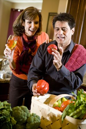 Mature couple in kitchen drinking white wine and looking at fresh vegetables photo