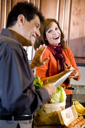couple laughing: Mature couple laughing in kitchen while husband cooks dinner Stock Photo