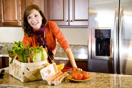 Happy attractive mature woman in kitchen with fresh produce on counter photo