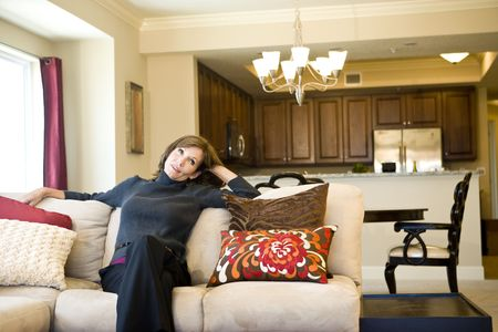 Attractive mature woman relaxing on couch in elegant modern living room photo