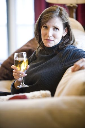 Attractive mature woman drinking white wine relaxing on couch in elegant modern living room photo