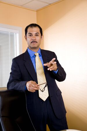 Serious middle-aged Hispanic businessman in standing boardroom making a point photo