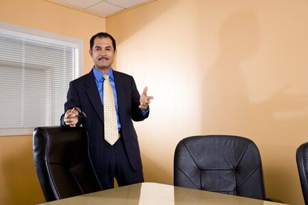 Confident middle-aged Hispanic businessman standing in boardroom photo