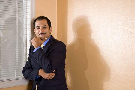 自信を持って中年ヒスパニック系ビジネスマンのあごに手でオフィスの窓のそばに立って 写真素材
