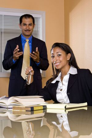Young African-American female office worker reading papers in boardroom with middle-aged Hispanic businessman standing behind