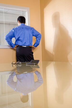 office space: Middle-aged Hispanic businessman in boardroom looking out office window